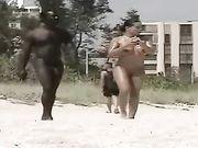 Nackte Frau mit einem nackten schwarzen Mann am Strand gefilmt
