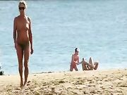 Eine reife Frau topless am Strand