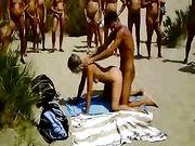 Paar macht Sex am Strand mit Publikum