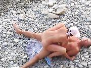 Ein FKK-Paar macht Sex am Strand und ein Voyeurist dreht sich